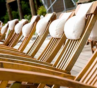 Teak wood chairs lined up on the beach
