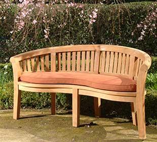 Teak wood love seat in a garden